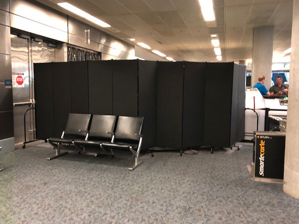 Portable wall configured around airport screening for privacy