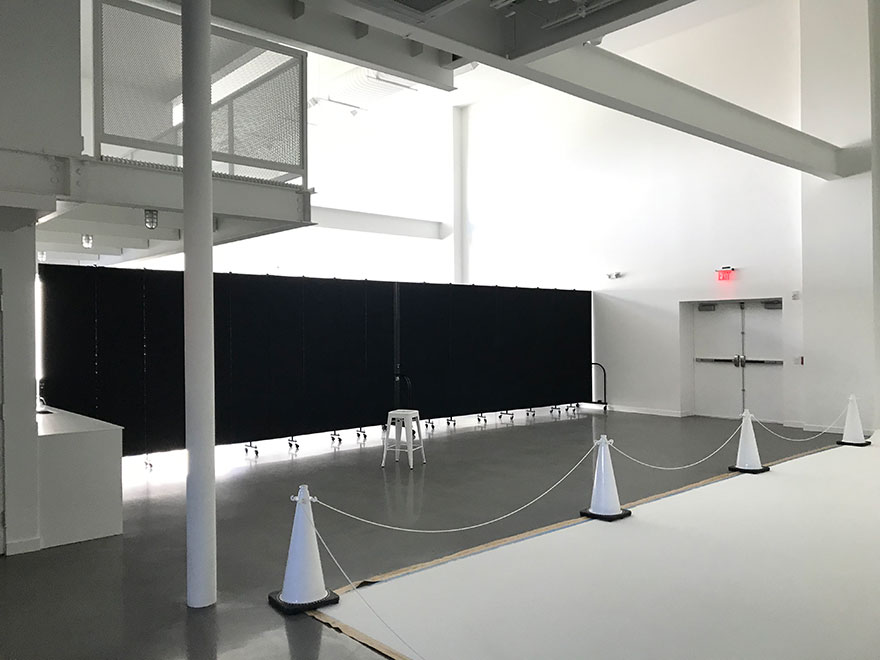 Large open white room is divided into two rooms by a set of black movable wall partitions