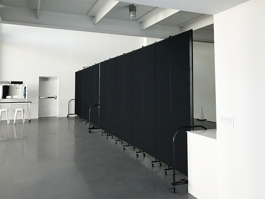 Black Screenflex room dividers create two area in a large white room