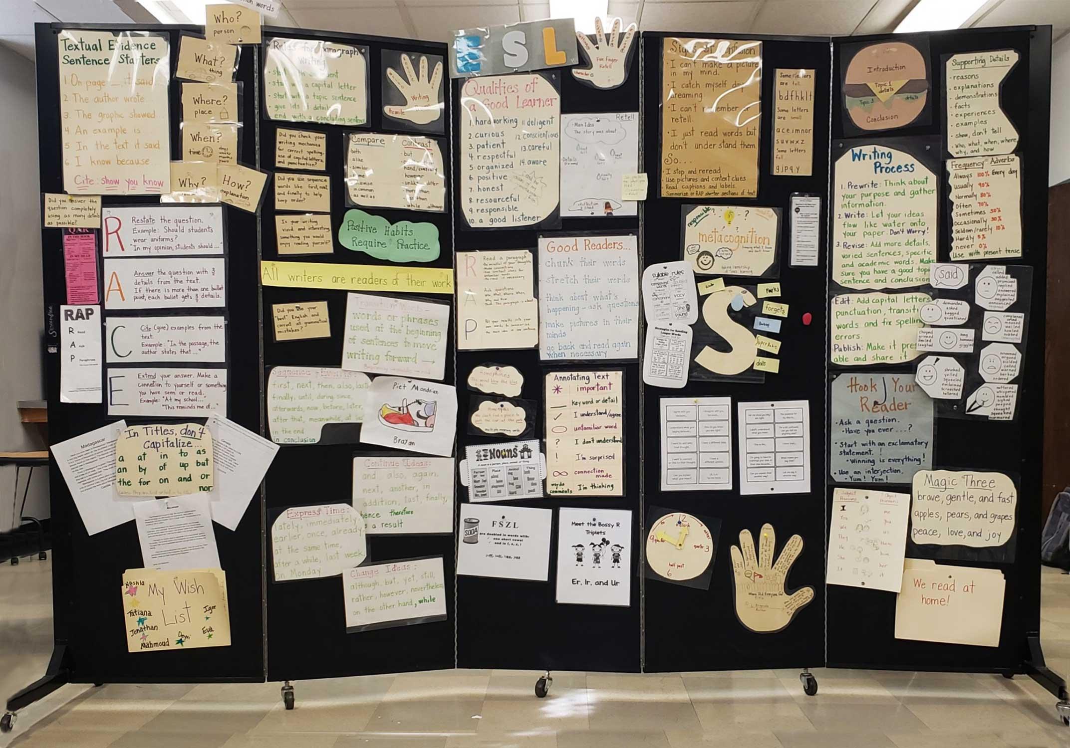 Student artwork covers a black 5-panel art display wall