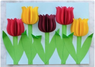 5 3D paper tulips on a blue piece of paper
