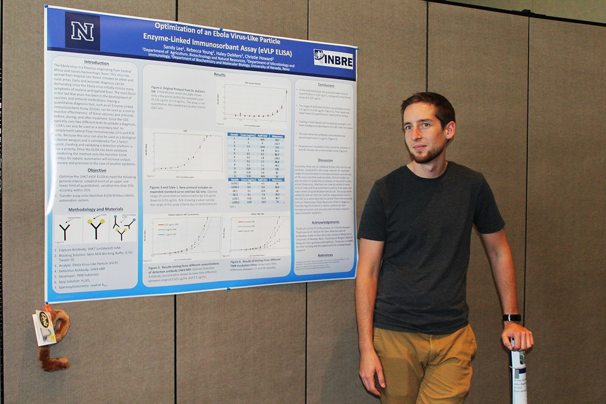 A man stands beside his college research poster on display