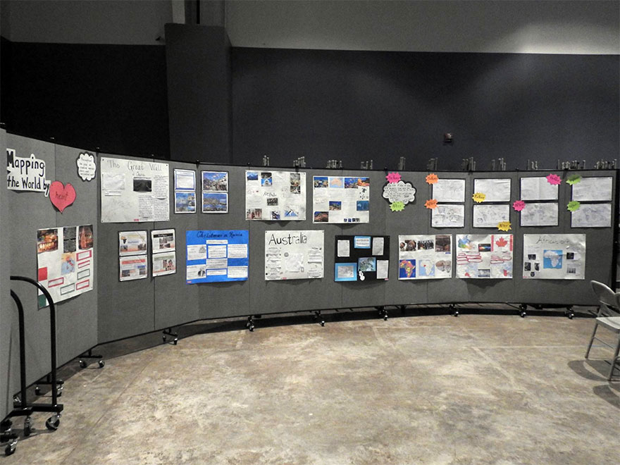 Student presentation posters displayed on a portable wall in a curved position