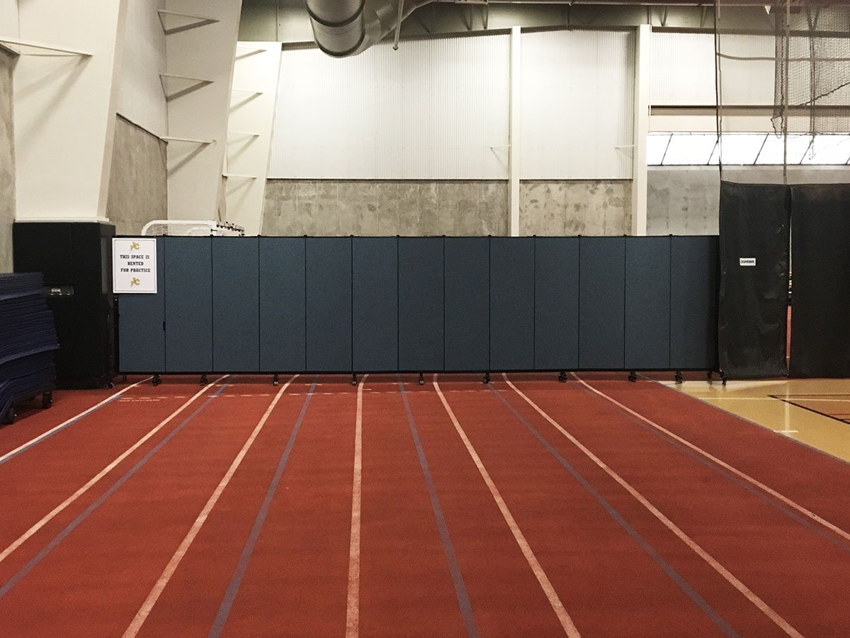 The back of a runner track is hidden by a long room divider