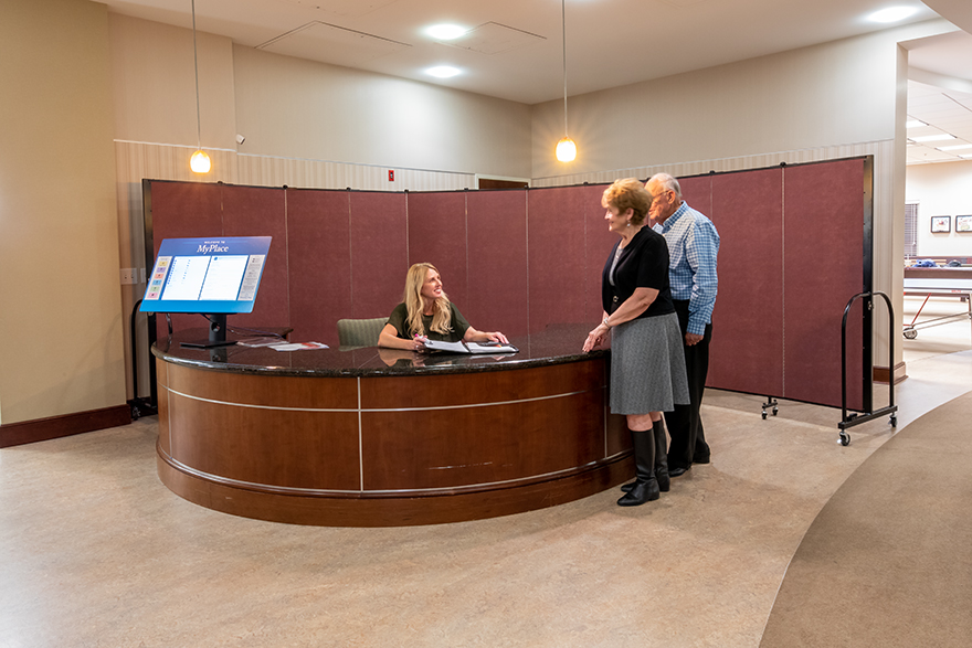 Sound absorbing wall behind a woman at a welcome desk talking with an older couple