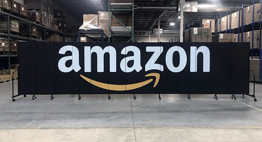 A black room divider with the Amazon logo printed across it