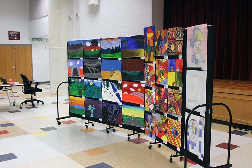 Young students' artwork on display for parent teacher conferences in a gym
