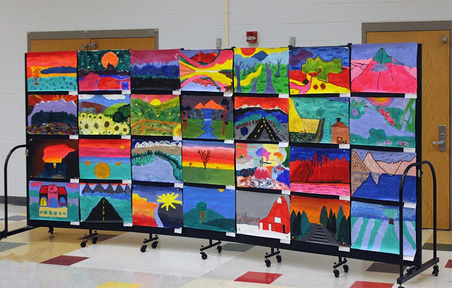 A black portable art display wall is covered with elementary school artwork.