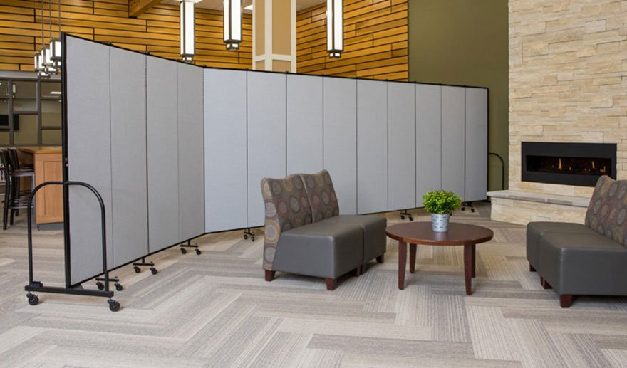 A grey portable wall separates two seating areas