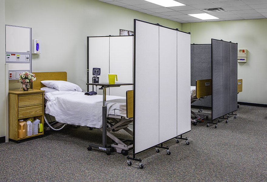 A set of medical privacy screens separate two hospital beds