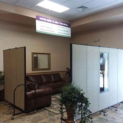 A set of room dividers with windows surround a pair of couches to create a church welcome center