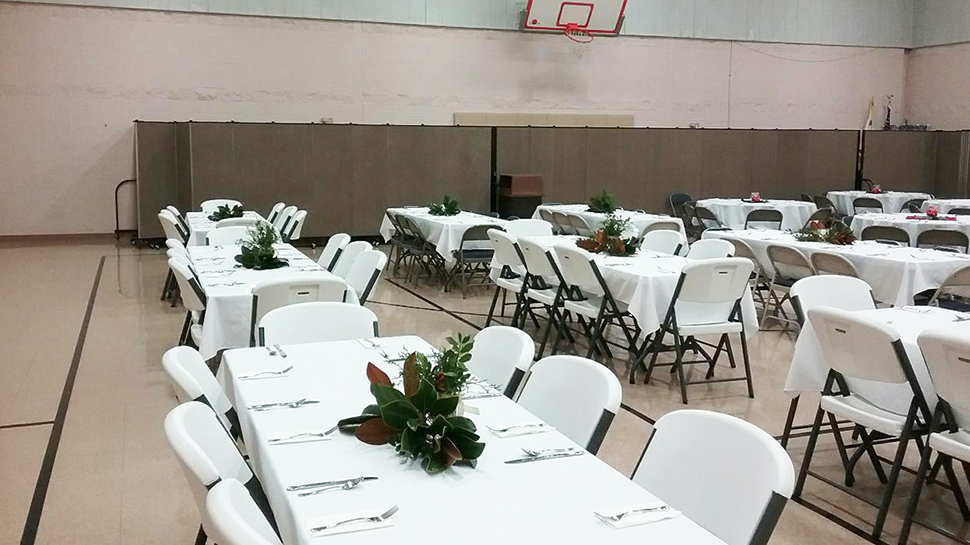 Food prep for a banquet is hidden behind a set of church portable walls