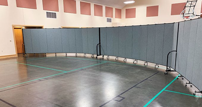 Portable wall divider separates a gymnasium into two classrooms