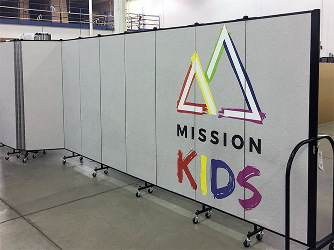 Portable partition with a custom logo greets students in at Mission Kids church program