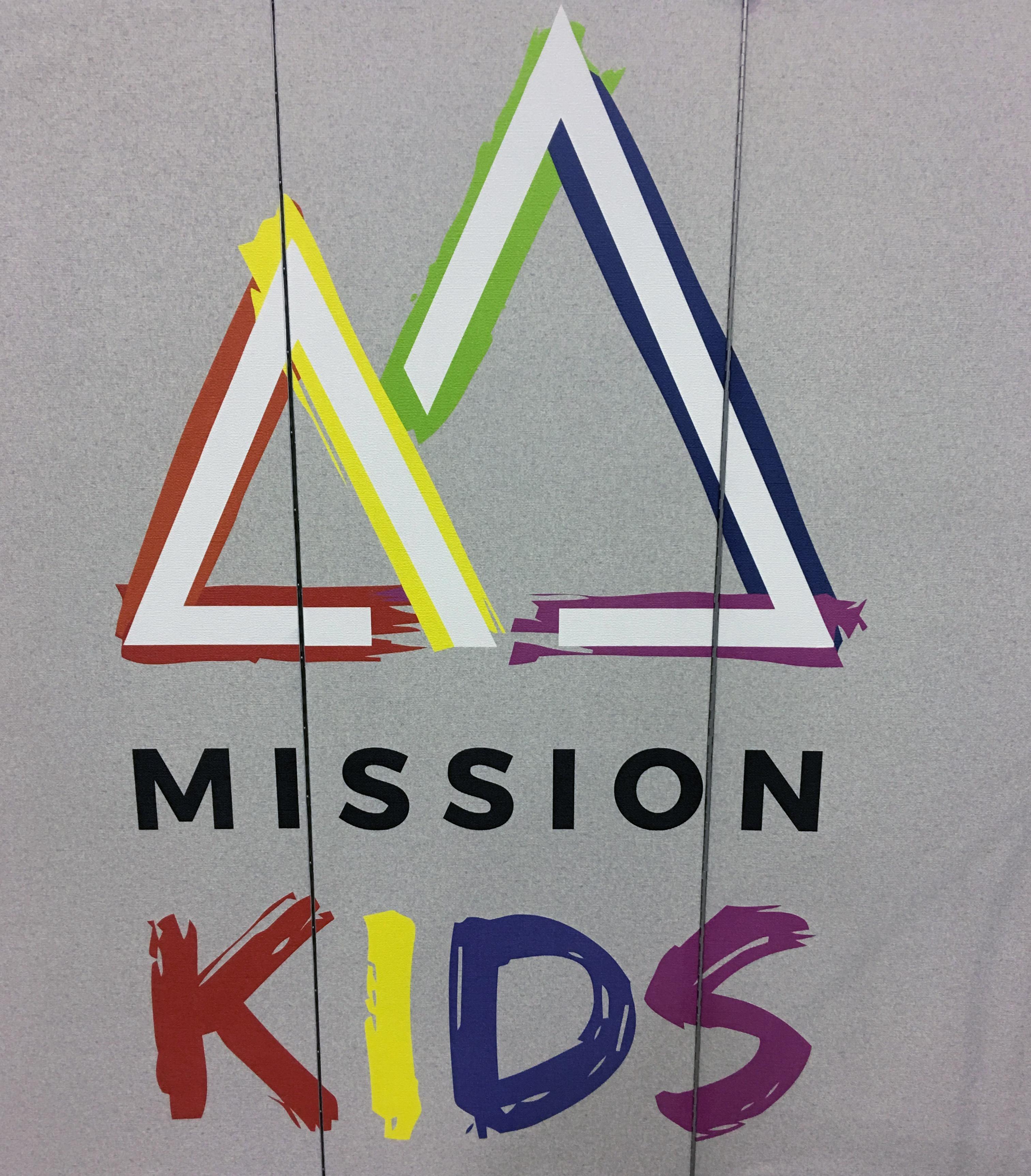 Colorful Mission Kids logo on a grey room divider