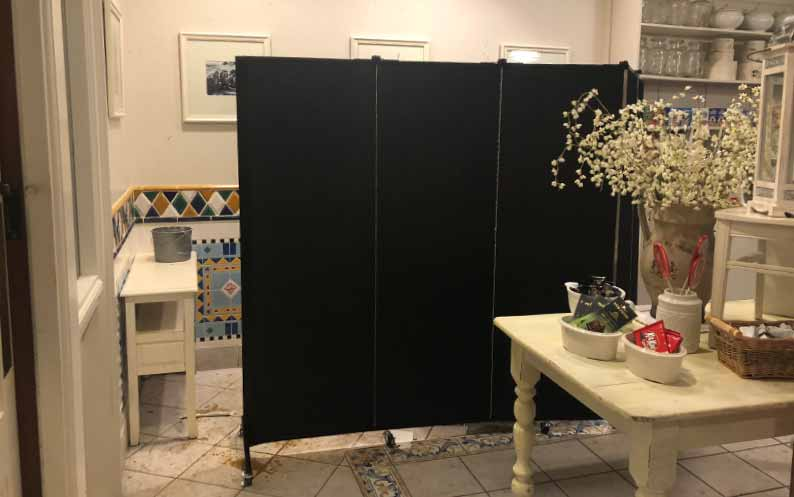 Black portable wall hides water damage in store