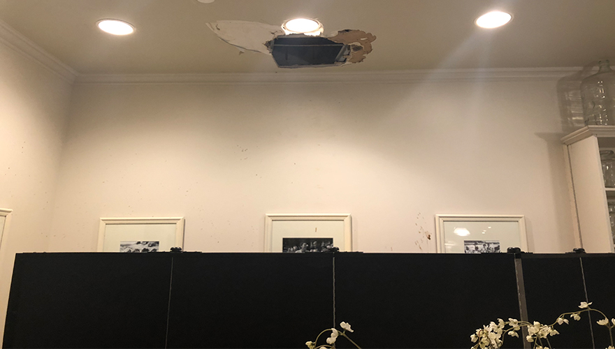 Water damage debris from ceiling hidden behind portable partition