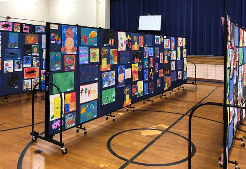 Three portable art display walls display artwork in a school gym