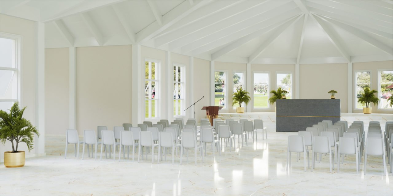 Before a room divider, several rows of white chairs in a church