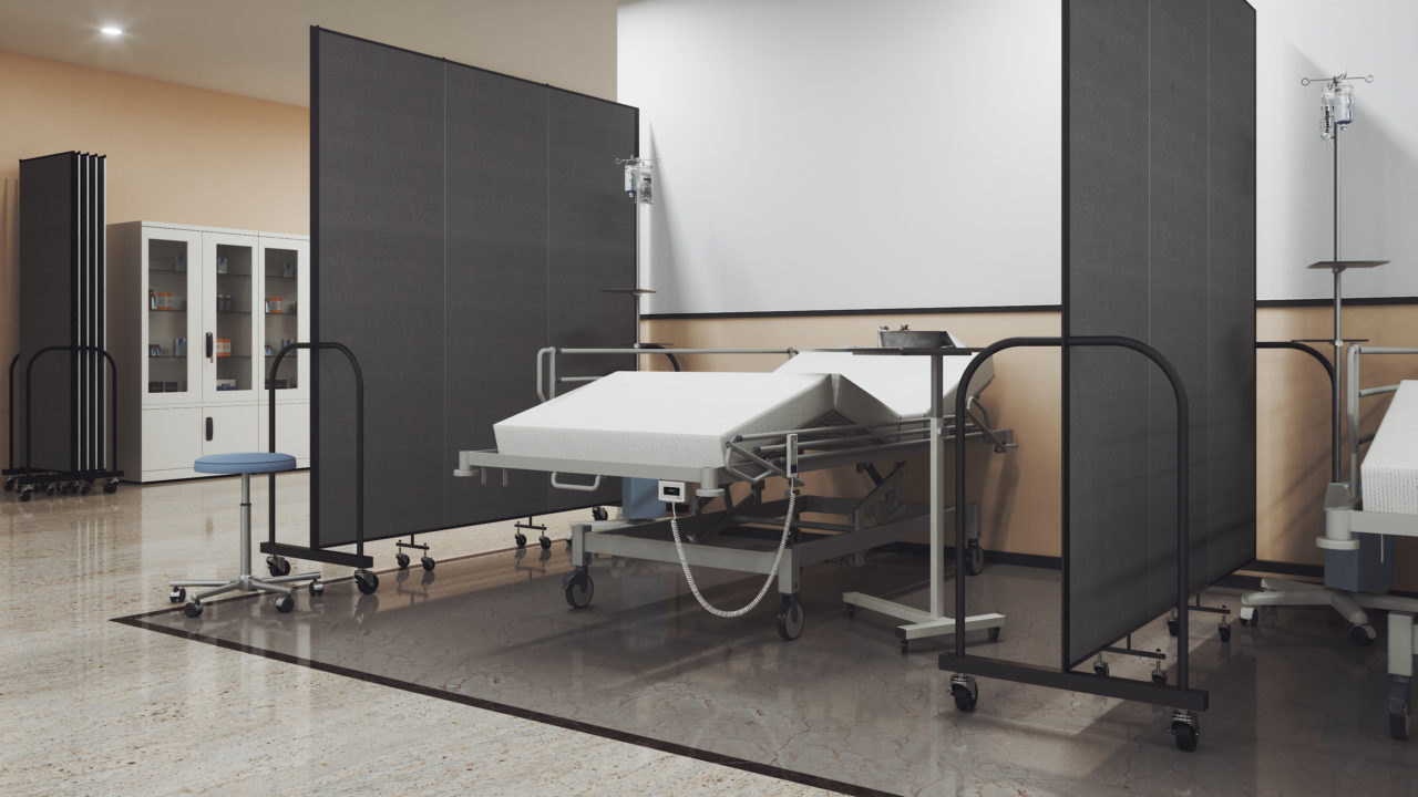 A hospital bed surrounded by room dividers on both sides