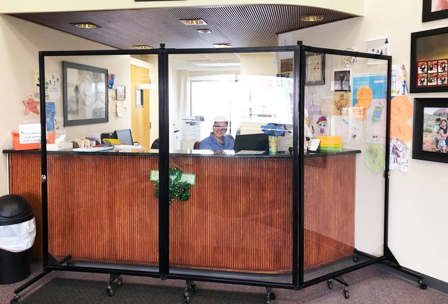 clear medical barrier in front of brown check-in desk and receptionist