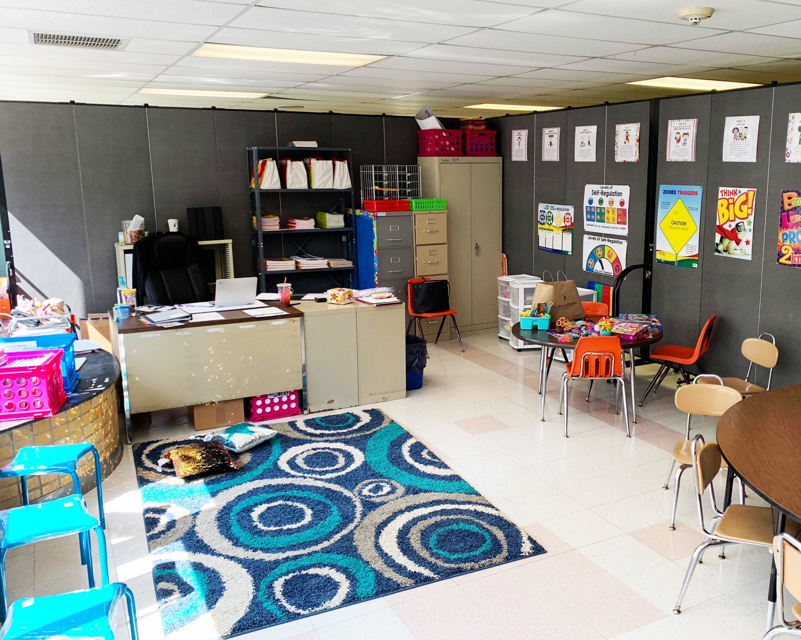 school supplies and furniture in front gray room divider