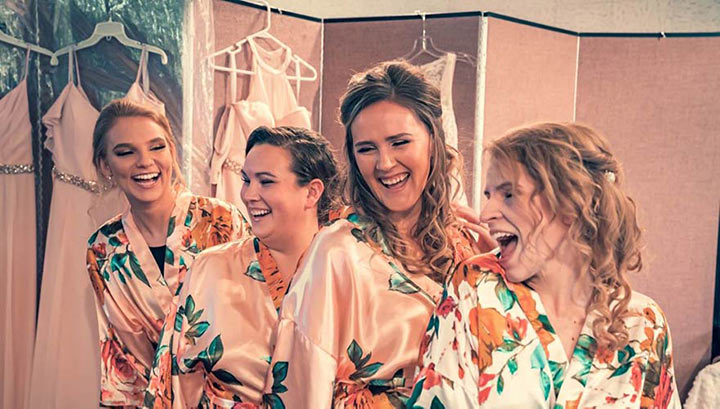 bride and her bridesmaids posing in front of a backdrop